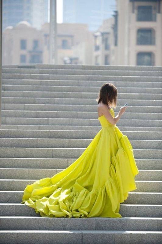 a strapless lemon colored wedding ballgown with a high low skirt and a train is bold and very modern