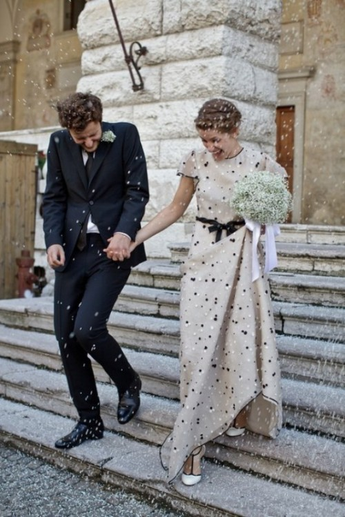 an off-white sheath wedding dress with polka dots, a high neckline and short sleeves plus a bow on the waist is very playful