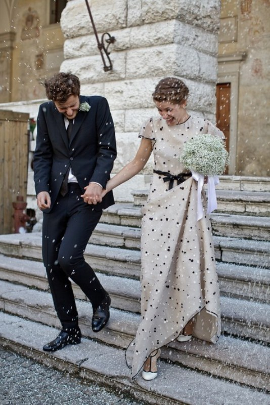 an off white sheath wedding dress with polka dots, a high neckline and short sleeves plus a bow on the waist is very playful