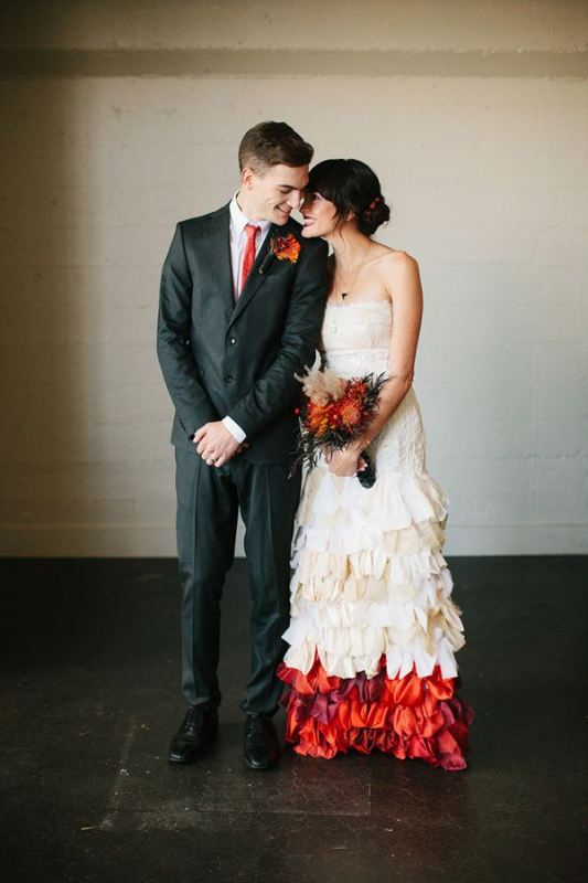 an off the shoulder sheath wedding dress with a draped bodice, a ruffle skirt with a colorful accent