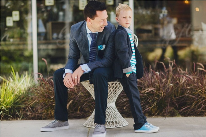 a groom wearing a midnight blue suit, grey sneakers and a navy printed tie looks chic yet not too formal