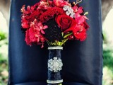 a bright red bridal bouquet with shiny touches and a navy wrap is a bold and contrasting idea