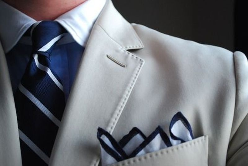 a groom's or groomsman look with a creamy jacket, a blue shirt, striped tie and handkerchief