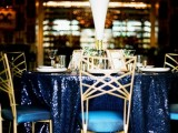 a midnight blue sequin tablecloth paired with white blooms and gold touches for a super chic look