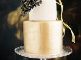 a shiny gold and white wedding cake topped with midnight blue berries for a contrasting touch