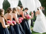 matching strapless midnight blue bridesmaid dresses and contrasting pink bouquet