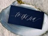 a midnight blue card in a seashell is a chic idea for a coastal wedding