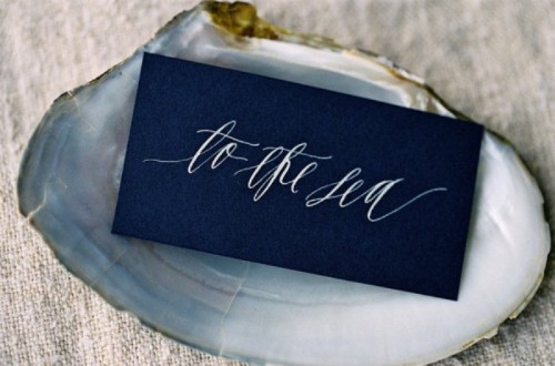 a midnight blue card in a seashell is a chic idea for a coastal wedding