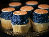 bright cupcakes with midnight blue cream and coral citrus toppers are a fun and bold idea for a wedding