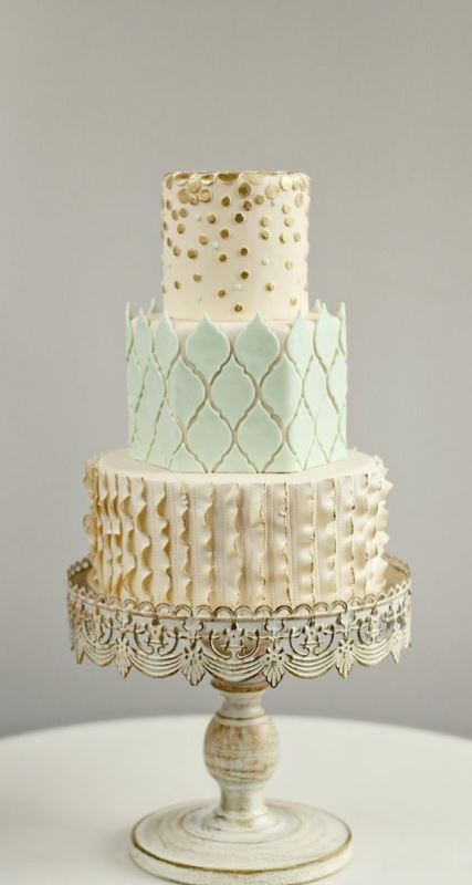 a whimsical pastel patterned wedding cake with a gold and mint tier, with polka dots, ruffles and geometric touches