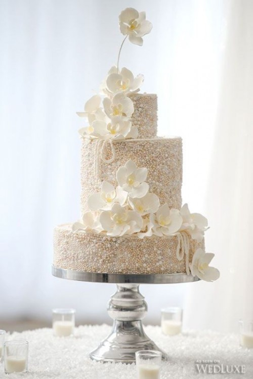 a beautiful white wedding cake fully covered with pearls and beads and with large white sugar blooms for a quirky wedding