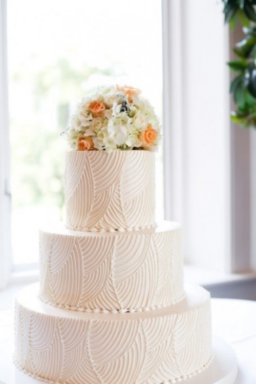 a white textural wedding cake with bright blooms on top is a cool idea for a modern wedding