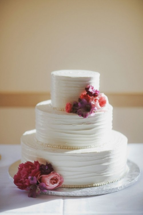 a white textural wedding cake decorated with bright fresh blooms for a simple and stylish wedding with a rustic touch