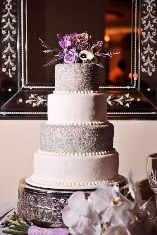a lilac wedding cake with plain and glitter tiers, bright blooms and feathers is a refined and chic dessert idea
