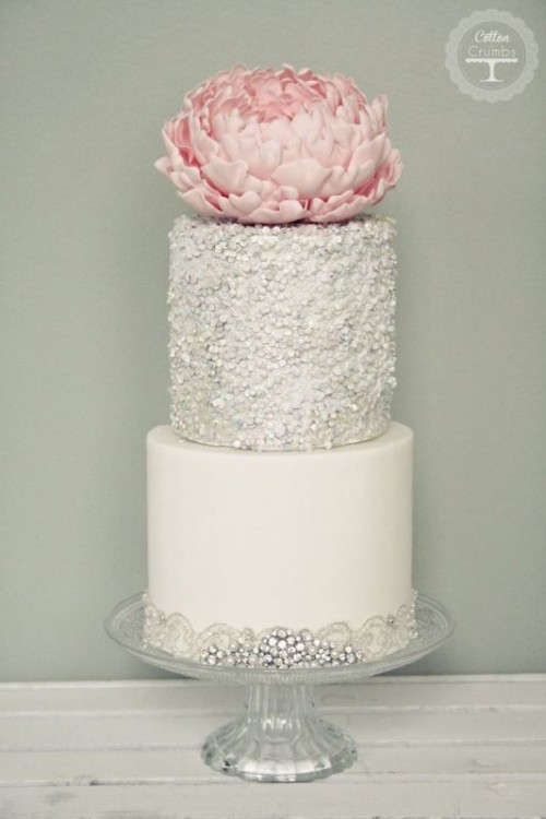 a white and silver wedding cake with a plain and polka dot tier, embellishments, lace and an oversized pink bloom