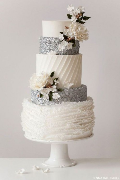 a white and silver wedding cake with striped, plain, glitter and ruffle tiers and sugar blooms and leaves