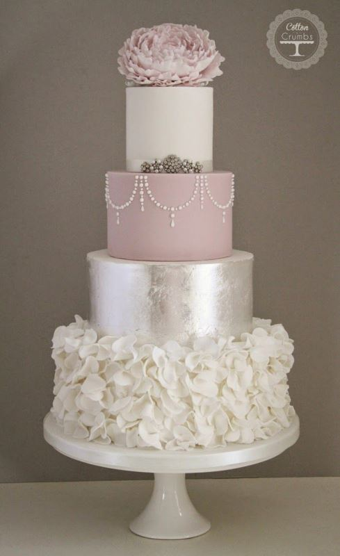 a very glam and chic wedding cake with pink, silver and white tiers - patterns, floral patterns and a pink sugar bloom on top