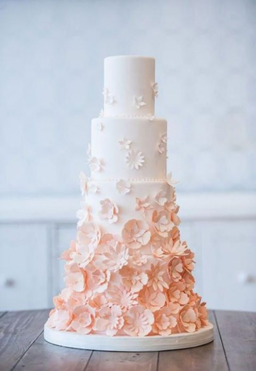 an ombre white to peachy wedding cake with lots of sugar blooms is very chic for spring or summer