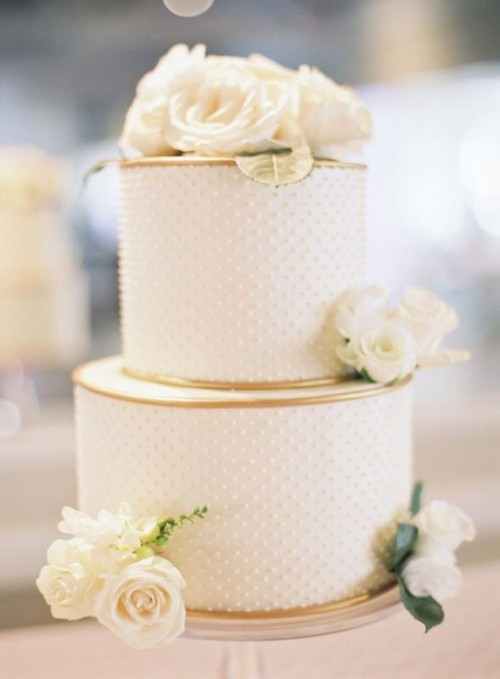 a white polka dot wedding cake with gold edge and fresh white blooms and leaves is very elegant