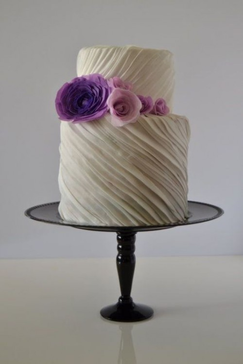 a white striped textural wedding cake with purple and pink sugar flowers is very bold and cool