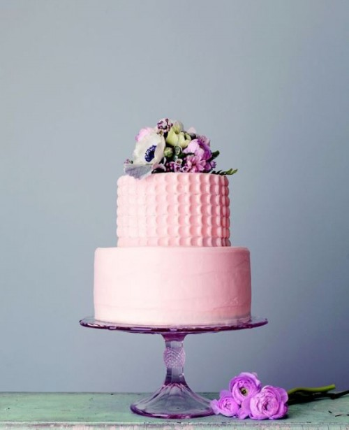 a light pink wedding cake with a textural patterned and a sleek tier plus fresh blooms on top