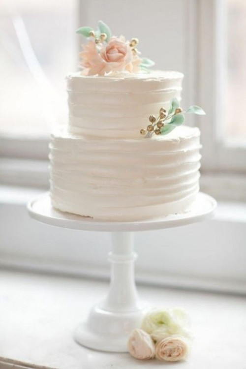 a white textural wedding cake with sugar blooms, leaves and berries is a cool and cute idea