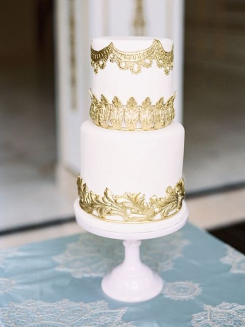 a white wedding cake with textural gold lace is a cool and fresh idea for a modern refined wedding
