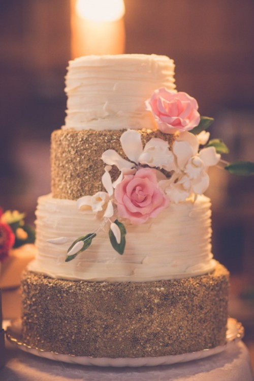 a white and gold textural wedding cake with glitter and ruffles, with sugar blooms and leaves