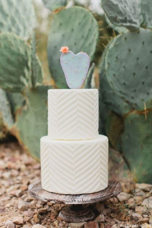 a white textural geometric wedding cake with a cactus on top for a modern or boho desert wedding