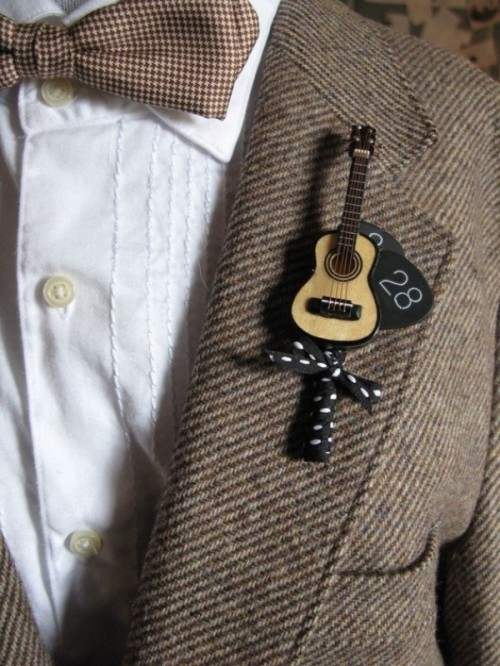 a creative guitar wedding boutonniere with a date and a bow is a perfect solution for a groom who loves music