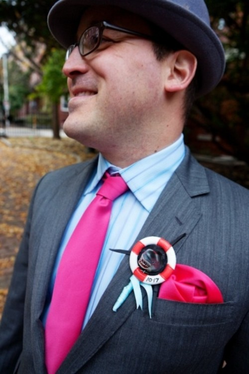 a creative wedding boutonniere of a striped life saver and some bright blue ribbon for a person whose job is connected to the sea