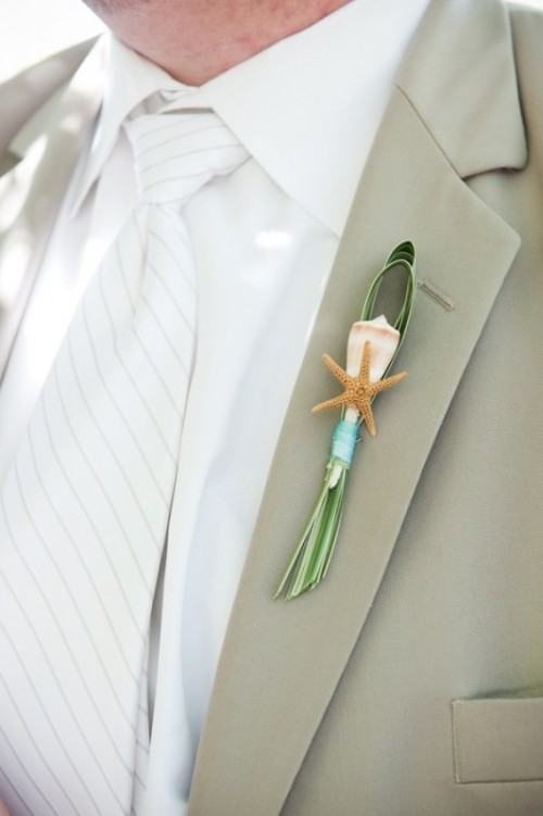 a seaside boutonniere of a seashell, a starfish, some grass and a ribbon is a cool idea for a coastal or beach wedding