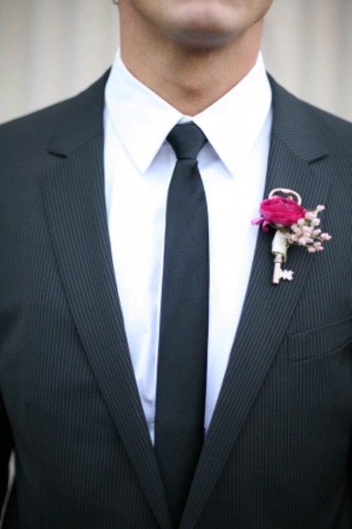 a cute and stylish boutonniere of a vintage key, a hot pink bloom and pink baby's breath is a very cool idea