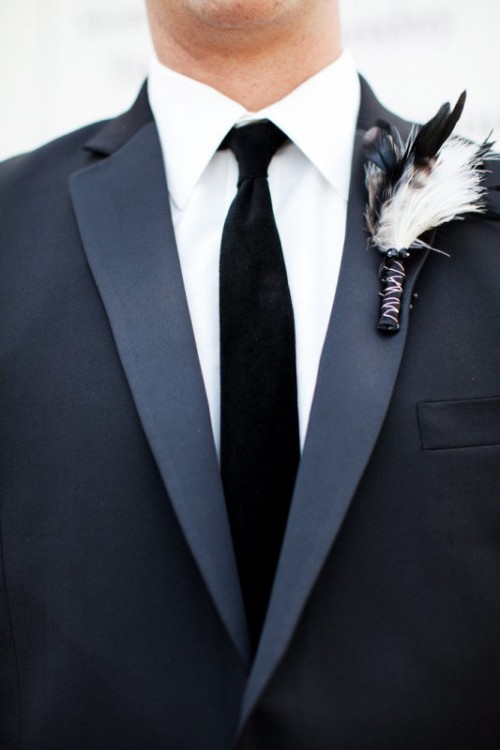 a feather wedding boutonniere with a black wrap will match a boho or Halloween groom style highlighting the time