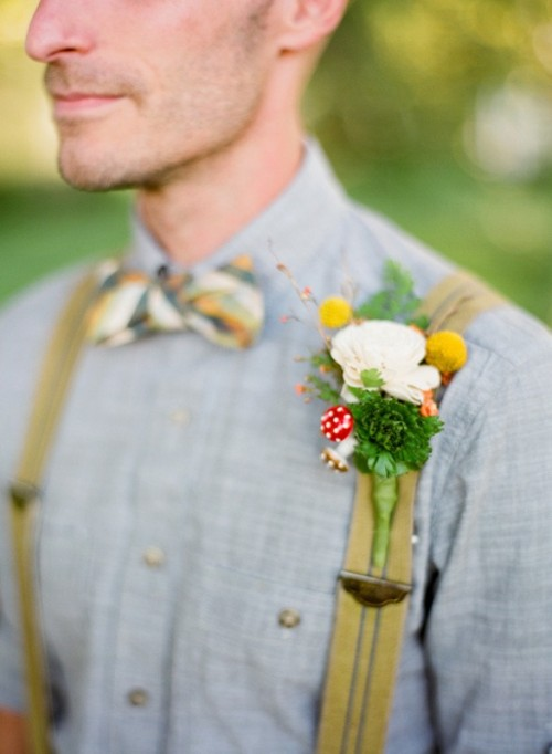 a unique summer woodland wedding boutonniere with a white bloom, billy balls, greenery, mushrooms and branches is pure fun