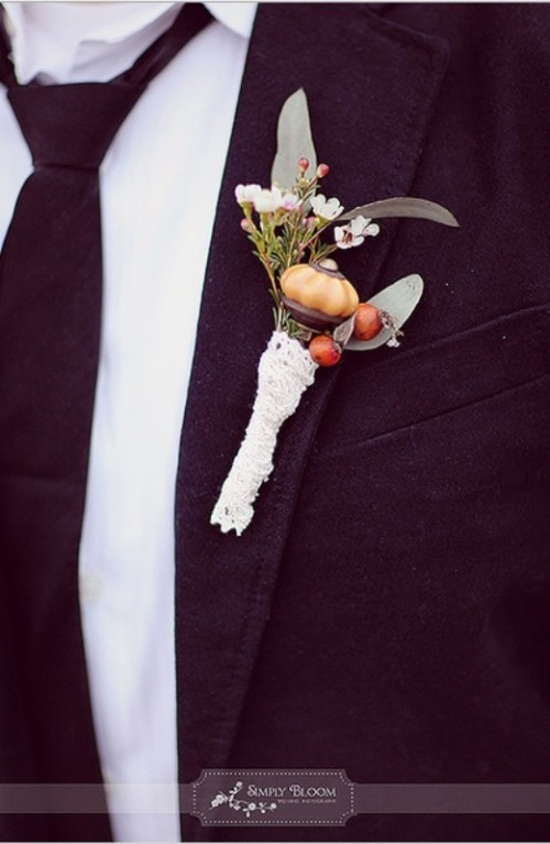 a unique fall boutonniere of greenery, white blooms and berries, a large amber piece and some lace wrap is a very interesting idea