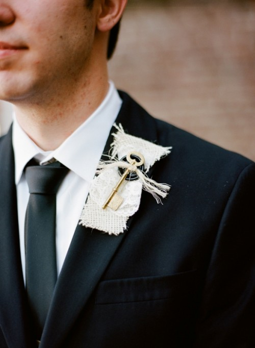 an unusual wedding boutonniere with white burlap, some printed fabric and a button and a large key shows off something personal for the groom