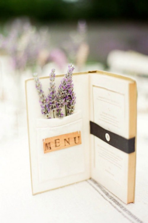 a book wedding menu with letters inside it and some lavender in a pocket is a fun and cute idea