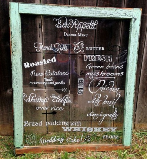 a giant wedding emnu written on an old window is a cool idea for a vintage and rustic wedding