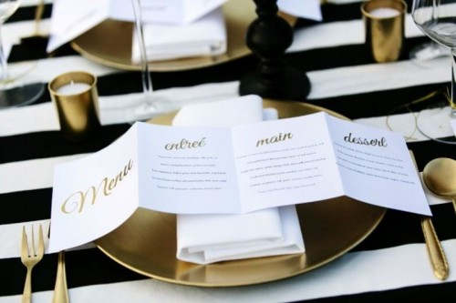 a folded menu with gold calligraphy is a stylish modern idea for a chic wedding