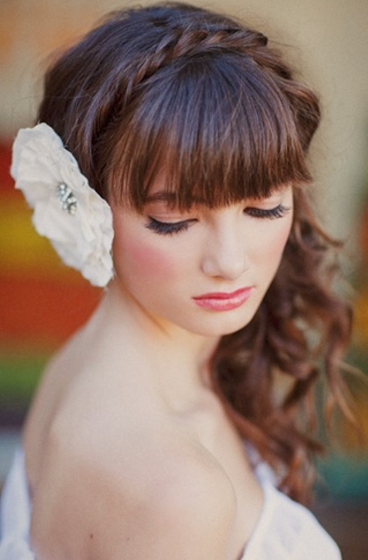a long wavy half updo with a braid on top and a full fringe bang plus a large bloom on the other side