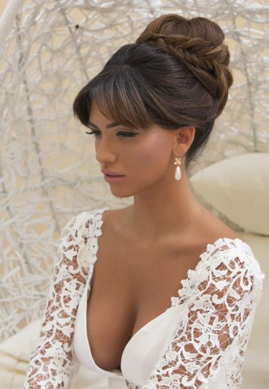 a formal updo with a bump, a top braided knot, bangs is a stylish and elegant idea