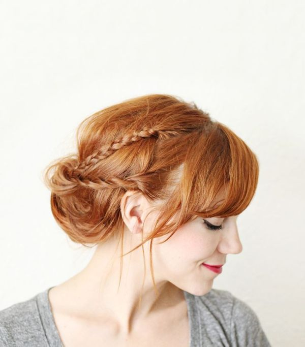 a low messy updo with two braids and bangs is a chic idea with a current trend   messy hair