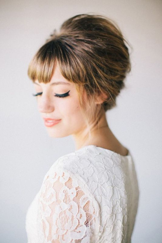 a full fringe bang with a retro inspired updo and matching makeup for a retro inspired wedding