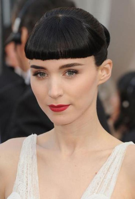 a very sleek updo with a short and curled bang for a minimalist bridal look