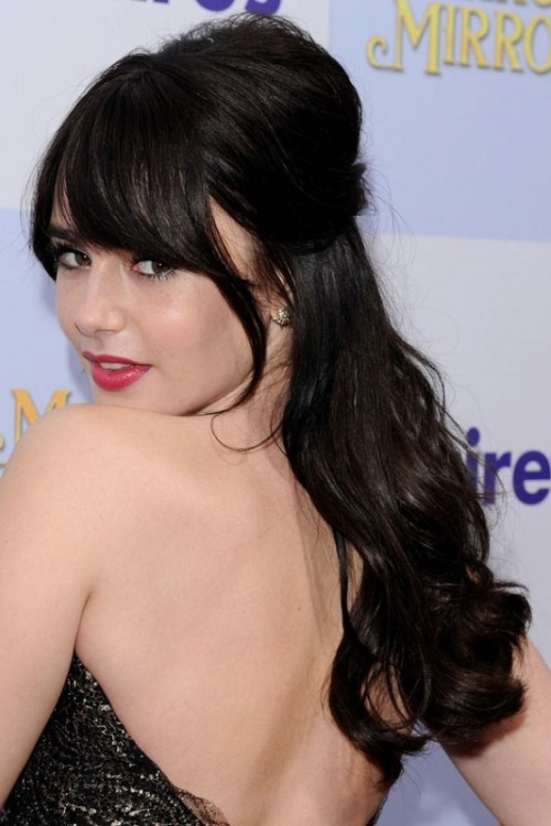 a long and wavy half updo with a bump and bangs is a classic hairstyle that fits many bridal styles