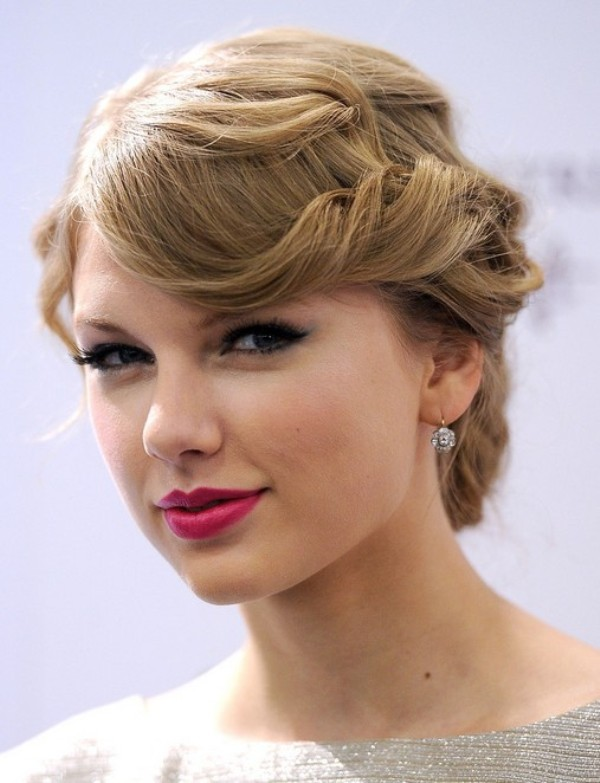 a wavy low updo with bangs is a stylish retro hairstyle for elegant and refined brides