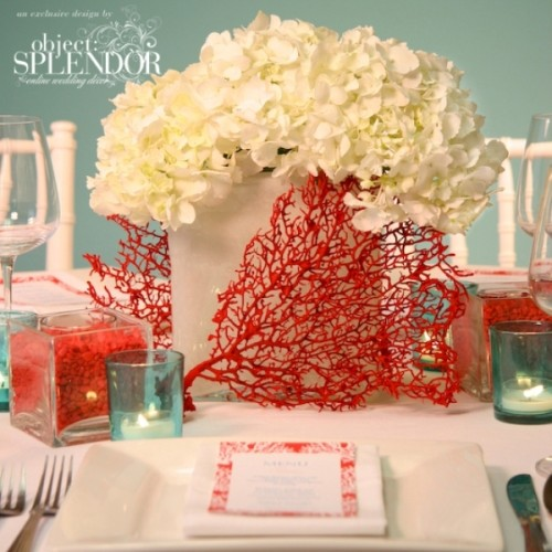 a frosted glass vase with white hydrangeas, corals, blue candle holders for a beach inspired wedding