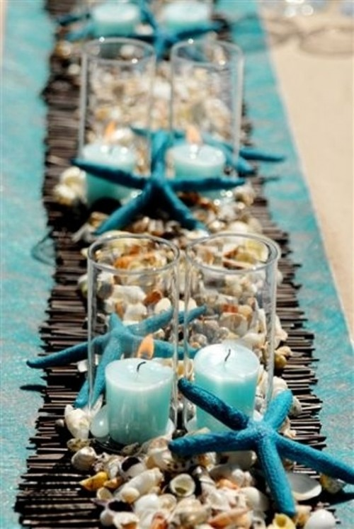 a bamboo runner, seashells and pebbles, starfish plus turquoise candles in candle holders