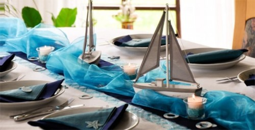 a blue table runner and boats plus candles for a beach or coastal wedding centerpiece